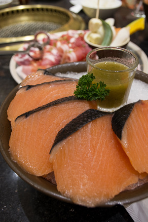 Sliced salmon meat served with cihili sauce for grilling photo
