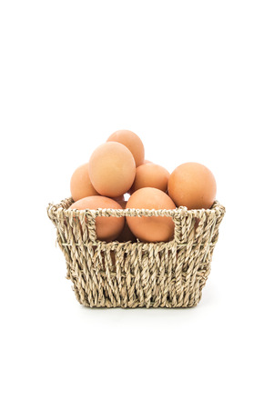 Fresh eggs in basket on white background photo