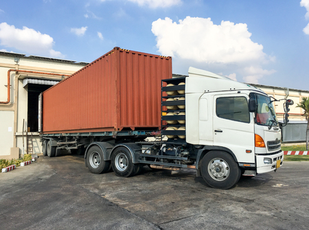 forwarder: Container truck loading goods at warehouse