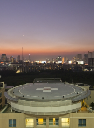 helicopter pad: A peak helipad on hospital building under sunset with city in background Stock Photo