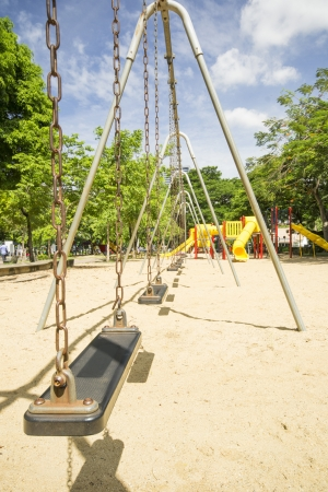 Closeup of swings in a children play area at park with blue sky photo
