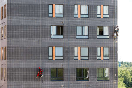 Two professional industrial climbers in helmet and uniform at work, washing building facade. Zdjęcie Seryjne