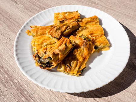 Plate with Turkish traditional borek with spinach and cheese, top view