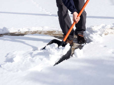 Close up image of worker shoveling snow from the sidewalk, winter concept