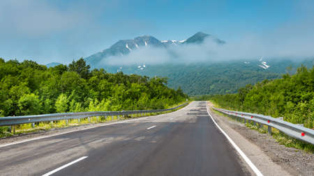 Straight empty asphalt automobile road in the Kamchatka Mountains, travel concept