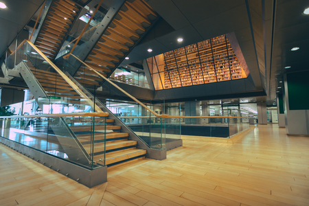 National library of Latvia. Modern architectural masterpiece. Multilevel floors with staircases and bookshelves in background.