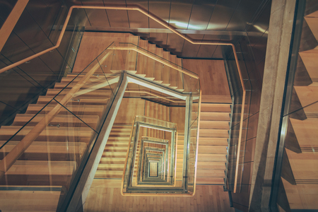 Spiral staircase from above with parquette floor. Square shaped stairs going downwards creating layers from each floor.
