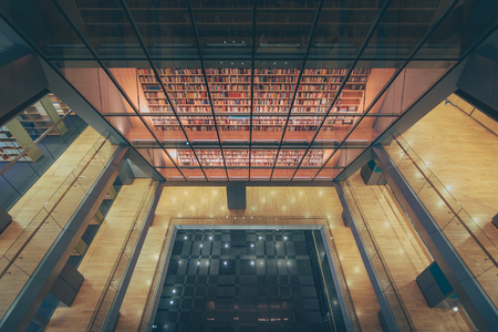 Huge bookshelf with tons of colorful books behind a glass wall. Collection of books in National library of Latvia. Modern architectural masterpiece.