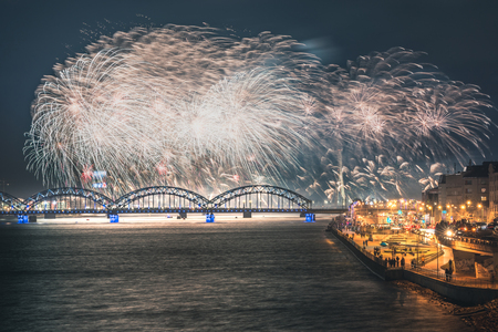 Colorful fireworks in Riga city with panoramic view over the river Daugava and railroad bridge. New year celebration. Stock Photo