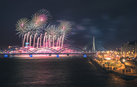 Colorful fireworks in Riga city with panoramic view over the river Daugava and railroad bridge. New year celebration. Editorial