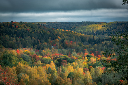 Picturesque view on valley of Gaujas national park. Trees changing colors in foothills.  Colorful Autumn day at city Sigulda in Latvia. Stock Photo