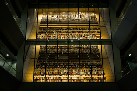 Huge bookshelf with tons of colorful books behind a glass wall. Collection of books in National library of Latvia. Modern architectural masterpiece. Zdjęcie Seryjne - 100495364