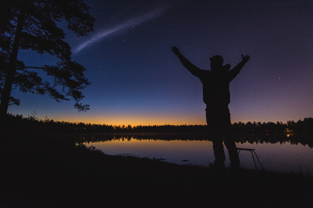 A man silhouette at the still lake in night time with a late sunset in background. Different poses towards dark blue sky.