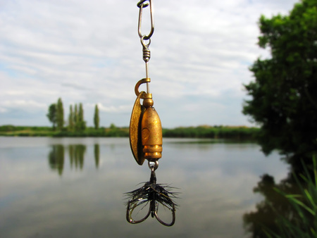 Fluffy fly fishing hook against the lake