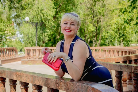 leaned: Happy woman in the park with a red handbag has leaned on a handrail