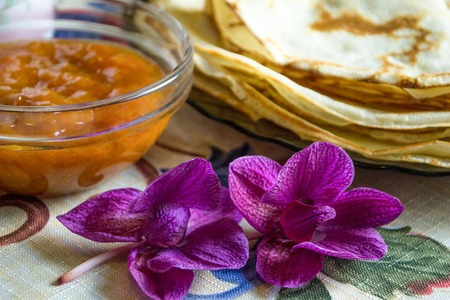 Orchid flowers in the foreground and delicious pancakes with jam on plate on a background