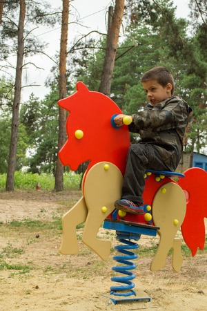 Happy baby child riding an orange horse at the playground Stock Photo