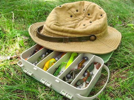 Row with a silicone baits for catching of fish is on the ground with fisherman s hat