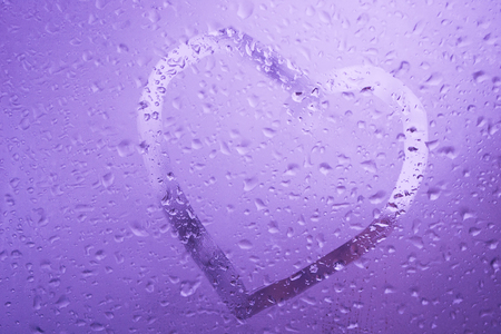 The symbol heart is drawn manually on the misted wet glass. Concept love, expectation, sadness, joy, hopes, nostalgia. Valentine day emotions.
