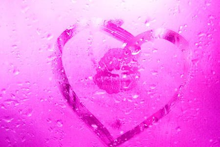 Lips print on glass in the draw heart at a wet window. Valentine day emotions. Pink, lilac color. Concept nostalgia, love, feelings, relations, lovers. Stock Photo