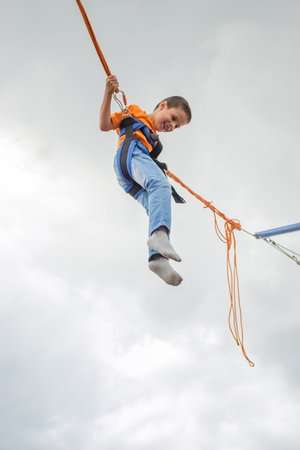 happy boy (6 years old) jumping on a blue sky background, bungee trampoline 写真素材