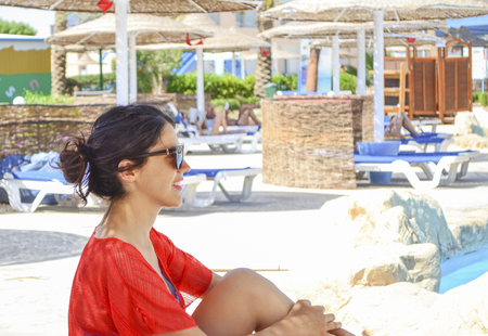 Tanned smiling young woman relaxing by the open air pool at egyptian hotel. Dressed in an orange pareo. Leisure concept. Stock fotó