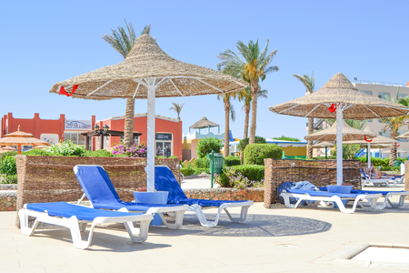 Hurghada, Egypt, May - 16th, 2018: free loungers at the poolside area at the hotel exterior in Egypt Editorial