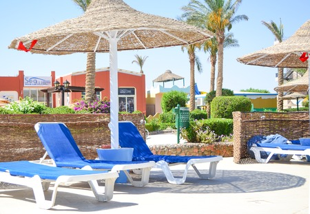 Free blue loungers with cane parasols at the poolside area at the hotel exterior in Egypt