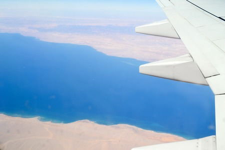 View from the porthole on the wing of the plane wich is flying over the Arabian desert and the Sinai Peninsula and the Red Sea between them. Altitude view of the desert and Red sea. 写真素材