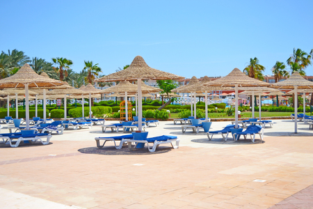 Hurghada, Egypt, May - 16th, 2018: Free blue loungers with cane parasols at the poolside area at the hotel exterior in Egypt Editorial