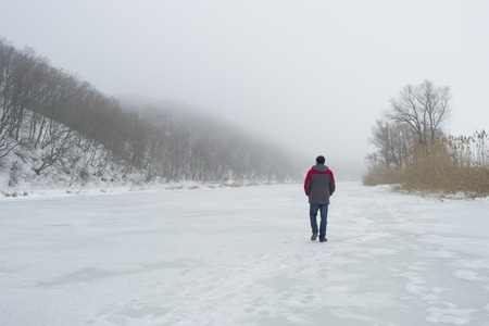A man walks alone goes into the distance on a frozen river in winter. Concept of seclusion and retreat.