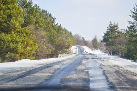 Melting snow outside of the city on the country road. Weather forecast for early spring. Melting snow, difficult road. Early spring in temperate climate.