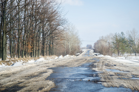 Melting snow outside of the city on the country road. Weather forecast for early spring. Melting snow, difficult road. Early spring in temperate climate. Spring is coming.