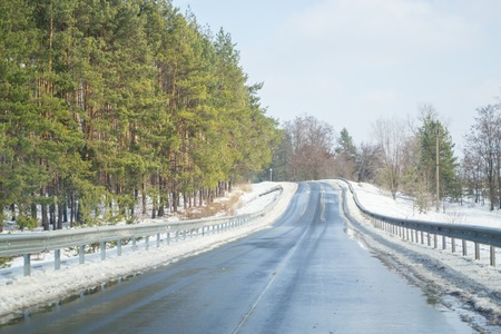 Melting snow outside of the city on the country road. Weather forecast for early spring. Melting snow, difficult road. Early spring in temperate climate. Spring is coming. Sunny spring weather. Beautiful pines on both sides of the road with bump stops.