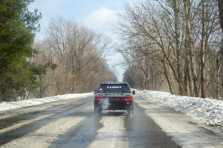 Severodonetsk, Ukraine - March 4th, 2018: View from the window of the car to the difficult snow-covered road with melting snow in the spring and a car rides ahead. Early spring, sunny day, difficult road. Weather forecast for early spring. Early spring in