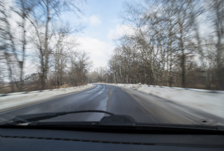 Blurred view from the car window, driving along the highway in early spring. Melting snow, difficult road. Speed, fast movement. Early spring in temperate climate. Soft focus.