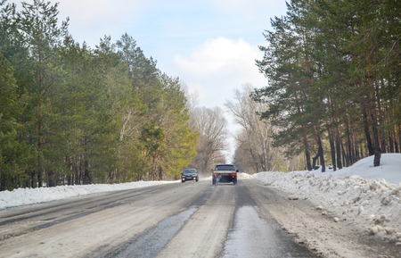 View from the window of the car to the difficult snow-covered road with melting snow in the spring. Stock Photo