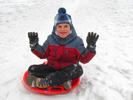 A boy of seven years old is riding down a hill on saucer sled, rejoices and waves his hands. Concept of winter activities, recreation and childrens entertainment.