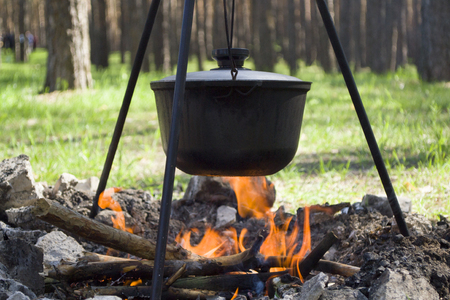 Pot over the fire in the forest. Cooking on a fire. Spring camping concept. Opening of the new tourist season. Banco de Imagens