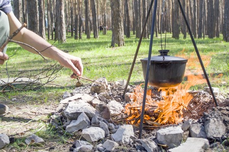 Pot over the fire in the forest. Cooking on a fire. Spring camping concept. Opening of the new tourist season. Man's hand puts firewood in the fire. Banco de Imagens