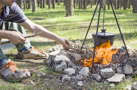Pot over the fire in the forest. Cooking on a fire. Spring camping concept. Opening of the new tourist season. Man's hand puts firewood in the fire. Man sitting by the fire, part of the body. Banco de Imagens