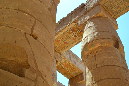 Ancient pillars of the Karnak temple. Bas-reliefs of hieroglyphs and ancient symbols on the columns. Fragments of central temple colonnade close up. Great hypostyle hall.