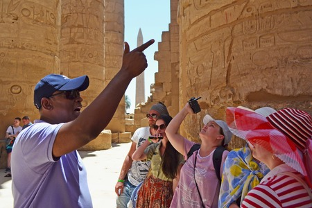A group of adult caucasian tourists visiting the interior of the Temple of Karnak in Luxor. Tourists visiting the central colonnade of the temple and rest in its shadow. Arabic guide shows ancient hieroglyphs and symbols.