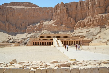 View of the valley in the desert and the ancient temple of Queen Hatshepsut carved into the rock. Pharaoh s memorial temple in Upper Egypt on the west bank of the Nile. Group of tourists on excursions. Stock fotó