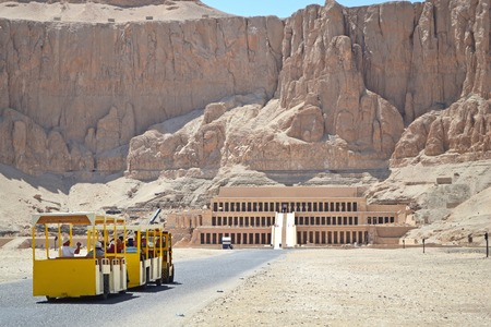 A tourist bus brings a group of tourists to inspect the ancient memorial complex of the Queen Hatshepsut Temple in Luxor. Pharaoh s memorial temple in Upper Egypt on the west bank of the Nile. Group of tourists on excursions.