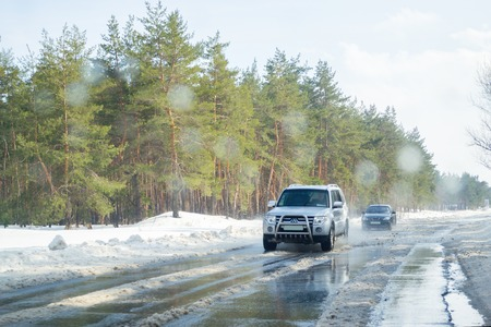 Severodonetsk, Ukraine - March 4th, 2018: View from the window of the car to the difficult snow-covered road with melting snow in the spring. Oncoming traffic. Early spring, sunny day, difficult road. Wet snow splashes on the windshield. Weather forecast