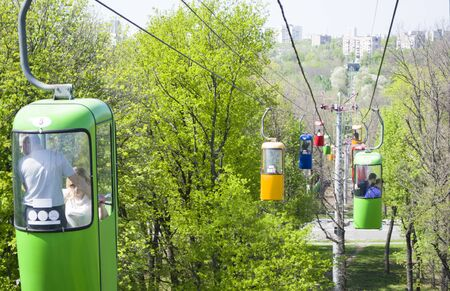 Three colourful cabins on rope in the city park. Panorama of cablecars - electric cabin transport.