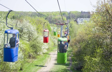 Lots of colourful cabins on rope in the city park. Panorama of cablecars - electric cabin transport. Stock Photo