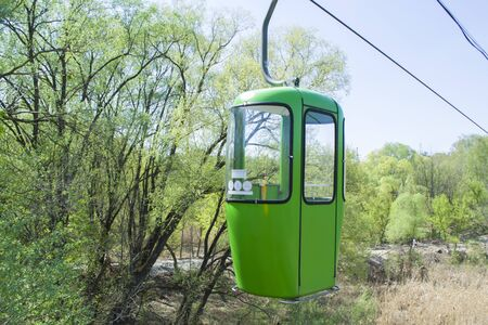 One green cabin on rope in the park. Close view of cablecar - electric cabin transport.