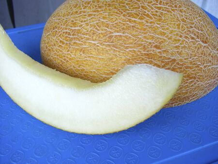 Ripe juicy melon on a blue cutting board. Slide from melon close up view.
